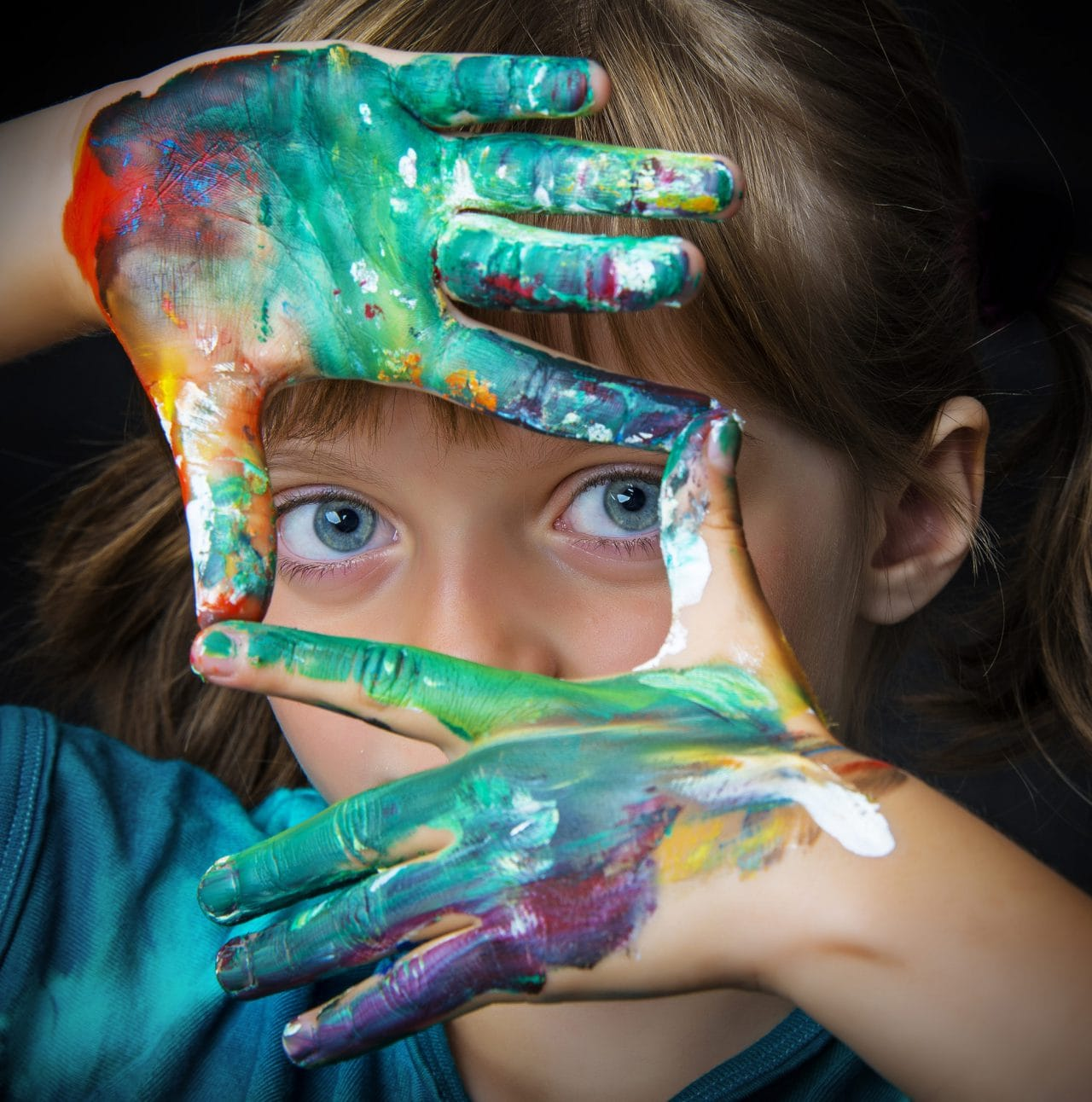 little girl with paint in her hand